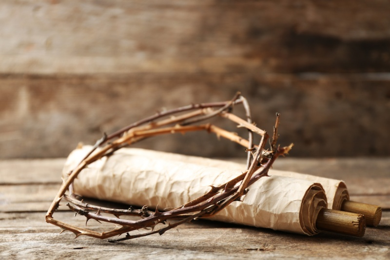 Crown of thorns and scroll on old wooden background